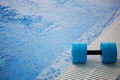 Kettlebell voor wateraerobics ligt op de rand van de pool Dichtbij het water Oefening, het zwemmen en gezond Royalty-vrije Stock Foto's