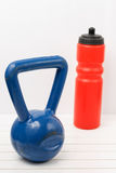 Kettlebell and water bottle on a white wooden floor Stock Photo