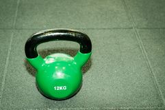 Kettlebell weight on the black gym floor with selective focus and film grain. Kettlebell weight on the black gym floor with selective focus and film grain stock photo