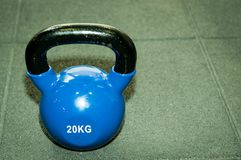 Kettlebell weight on the black gym floor with selective focus and film grain. Kettlebell weight on the black gym floor with selective focus and film grain royalty free stock image
