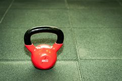 Kettlebell weight on the black gym floor with selective focus and film grain. Light kettlebell weight on the black gym floor with selective focus and film grain royalty free stock image