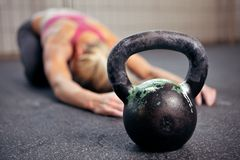 Kettlebell Workout. Young woman stretching her back after a heavy kettlebell workout in a gym Royalty Free Stock Photo
