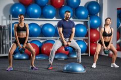 Kettlebell workout in the gym. Fitness instructor with two girls working out with kettlebell Stock Photography