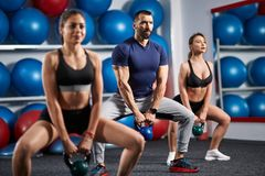 Kettlebell workout in the gym. Fitness instructor with two girls working out with kettlebell Royalty Free Stock Image