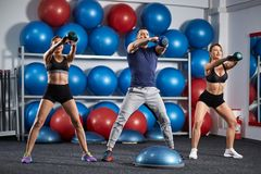 Kettlebell workout in the gym. Fitness instructor with two girls working out with kettlebell Royalty Free Stock Photos