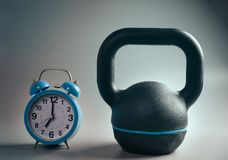 Kettlebell workout time. Close up of a kettlebell and a clock isolated iron gym muscle health sport shape lifting lifestyle bodybuilding strong weight white royalty free stock images