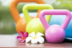 Kettlebell, yoga mat and flower on the table Royalty Free Stock Photos
