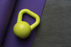 Kettlebell and yoga mat on table. Fitness healthy and sport concept Stock Photography