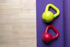 Kettlebell with yoga mat on wooden table Royalty Free Stock Photos