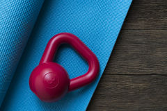 Kettlebell and yoga mat on wooden table Royalty Free Stock Photography