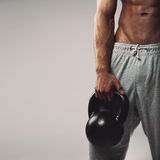 Kettlebell in young man's hand Royalty Free Stock Photo