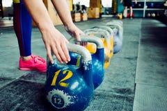 Kettlebellclub Het meisje wordt bereid om een training met gewichten te doen, lange cyclus duwen royalty-vrije stock afbeeldingen