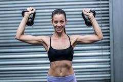 Kettlebells мышечной женщины поднимаясь Стоковые Изображения RF