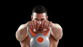Kettlebells серьезного мышечного человека поднимаясь акции видеоматериалы