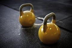 Kettlebells amarillos en un gimnasio del crossfit fotos de archivo