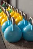 Kettlebells coloridos em seguido em um gym Fotos de Stock Royalty Free