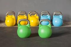 Kettlebells coloridos em seguido em um gym - centre-se sobre o kett dianteiro Fotografia de Stock