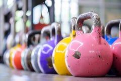 Kettlebells coloridos en fila en un gimnasio Foto de archivo