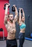 Kettlebells de levage d'un couple musculaire Photos stock