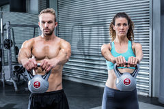 Kettlebells de levage d'un couple musculaire images stock