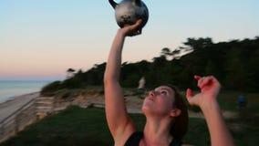 Kettlebells de levantamento da mulher bonita na praia vídeos de arquivo