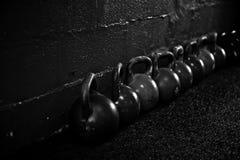 Kettlebells en el piso en un gimnasio B/W del crossfit foto de archivo
