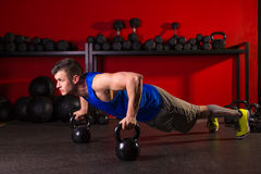 Kettlebells push-up man strength gym workout. Kettlebells push-up man strength pushup exercise workout at gym royalty free stock photography