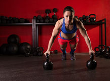Kettlebells push-up woman strength gym workout. Kettlebells push-up woman strength pushup exercise workout at gym royalty free stock image