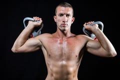 Kettlebells senza camicia sicuri della tenuta dell'atleta Fotografie Stock