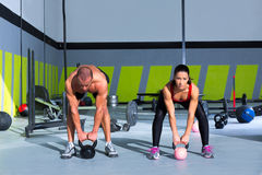 Kettlebells swing crossfit exercise man and woman. Workout at gym Stock Photos