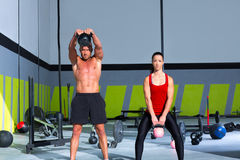 Kettlebells swing crossfit exercise man and woman. Workout at gym Royalty Free Stock Photos