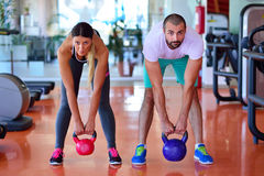 Kettlebells swing exercise man and woman workout at gym Royalty Free Stock Photography