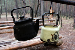 Kettles in forest camp Stock Images