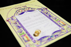 Ketubah - marriage contract in jewish religious tradition. Wedding rings and Ketubah - a prenuptial agreement in jewish religious tradition Stock Image