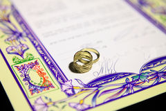 Ketubah - marriage contract in jewish religious tradition. Wedding rings and Ketubah - a prenuptial agreement in jewish religious tradition Royalty Free Stock Photography