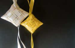 White and yellow ribbons of ketupat with dark background