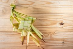 Ketupat Pouches on Wooden Background - Ketupat is a type of dumpling made from rice packed inside a diamond-shaped container of