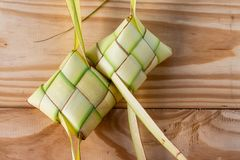Ketupat Pouches on Wooden Background - Ketupat is a type of dumpling made from rice packed inside a diamond-shaped container of stock photos