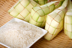 Ketupat rice dumpling and rice on traditional woven tray. Ketupat normally serve during serve during Hari Raya Aidilfitri in Malaysia and Indonesia Stock Photo
