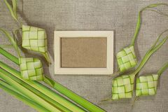Ketupat rice dumpling with wooden frame on jute texture background. royalty free stock images