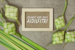 Ketupat risklimp med formuleringarna av Selamat Hari Raya Aidilfitri p? jutetexturbakgrund arkivbilder