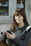 Keuken die iphone gebruikt Stock Afbeeldingen