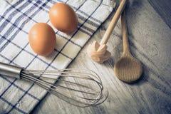 Keuken die met 2 Eieren, Handdoek, Houten Lepel en Querl en een Eggbeater op een Lijst plaatsen stock fotografie