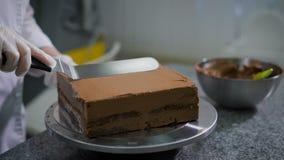 Keuken in een snoepwinkel De vrouw in keuken kookt chocoladecake De banketbakker in handschoenen en een witte vorm heeft stock footage