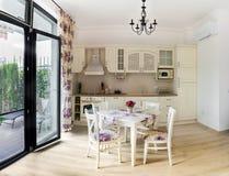 Keuken en kabinetten en lijst met stoelen royalty-vrije stock afbeelding