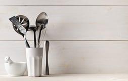 Keuken kokende werktuigen in witte kop met stamper en mortier  stock afbeelding