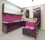 Keuken met de shinny deuren van Bourgondië en roze eiland Royalty-vrije Stock Foto