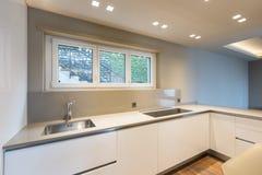 Keuken met modern wit meubilair en recentste generatieapplia royalty-vrije stock afbeeldingen