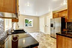 Keuken met zwarte granietbovenkanten en houten kabinetten Royalty-vrije Stock Foto's
