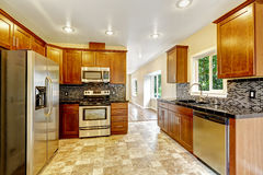 Keuken met zwarte granietbovenkanten en houten kabinetten Stock Afbeelding